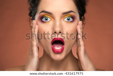 Shocked surprised pretty woman with bright make up - stock photo