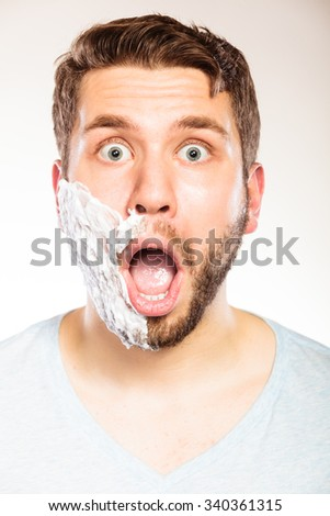 Shocked surprised young man with shaving cream foam on half of face beard. Handsome guy preparing to shave. Skin care and hygiene. - stock photo