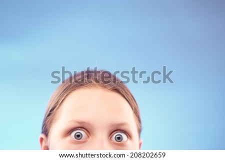 Shocked teen girl. Half of the face - stock photo