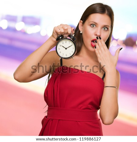 Shocked Woman Holding Alarm Clock against a city by night