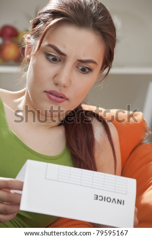 shocked woman holding bill or invoice at home - stock photo