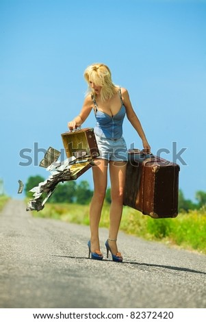 Shocked woman holding  opening suitcases with cash on countryside road - stock photo