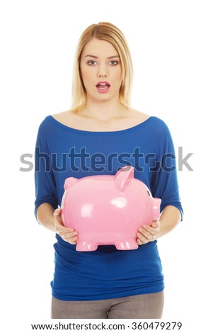 Shocked woman holding piggybank.