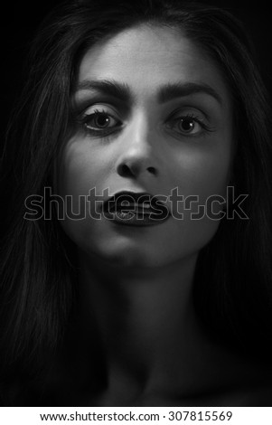 shocked woman in dark, monochrome image - stock photo