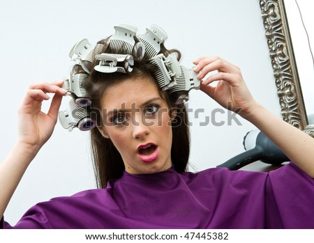 shocked woman in hair salon with curlers in her hair - stock photo
