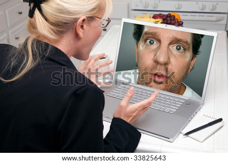 Shocked Woman In Kitchen Using Laptop with Strange Man on Screen. Screen image can easily be replaced using the included clipping path. - stock photo