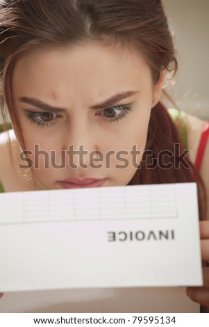 shocked woman looking at bill amount letter - stock photo