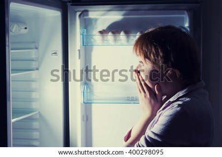 shocked woman looking into refrigerator - stock photo