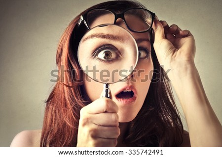 Shocked woman looking through a magnifying glass - stock photo