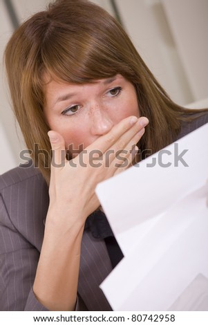 shocked woman reading a letter - bad news or fired - stock photo