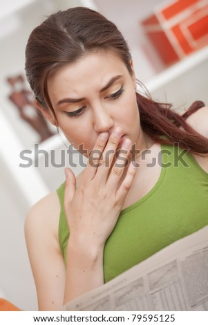 shocked woman reading bad news in newspaper - stock photo