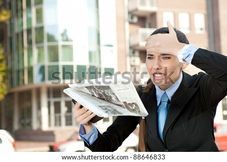 shocked woman reading newspaper on street, oh no bad news - stock photo