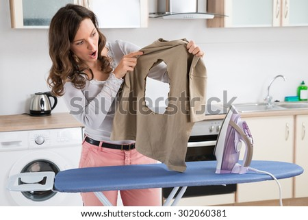Shocked Woman With Burned Iron Cloth Standing Near The Ironing Board At Home - stock photo