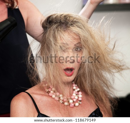 Shocked woman with messy hair from blow dryer - stock photo