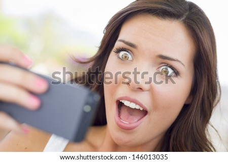 Shocked Young Adult Female Reading Cell Phone Outdoors on Bench. - stock photo