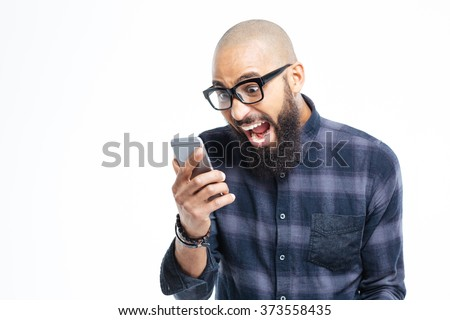 Shocked young african american baldheaded man with beard using mobile phone and shouting  - stock photo