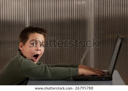 Shocked young boy reacting to info on a laptop computer