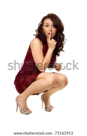 Shocked young brunette in red dress. Isolated on white - stock photo