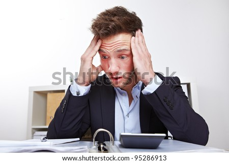 Shocked young business man in office looking at files