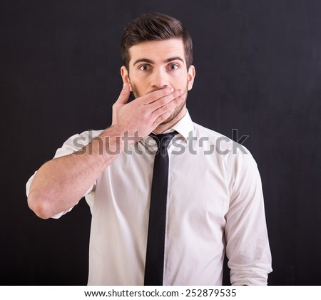 Shocked young man in shirt and tie is covering mouth with hand and looking at the camera, standing on the dark background. - stock photo