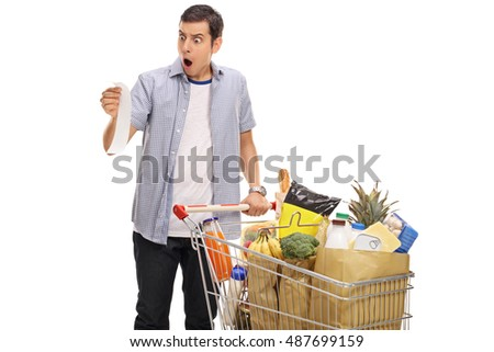 Shocked young man looking at a store receipt isolated on white background