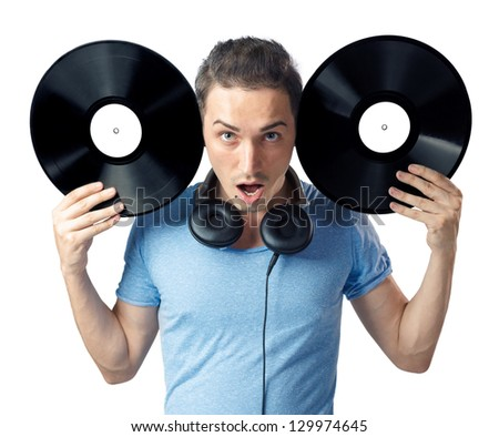Shocked young man posing to camera while holding two black vinyl disks near his head. Isolated on white background.