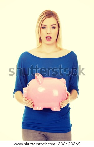 Shocked young woman holding piggybank.
