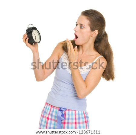 Shocked young woman in pajamas looking on alarm clock