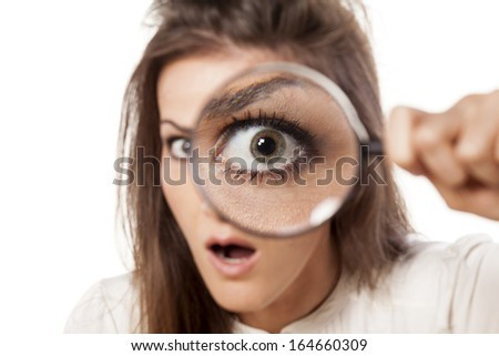 shocked young woman looking through a magnifying glass - stock photo