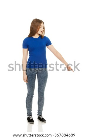 Shocked young woman pointing down. - stock photo