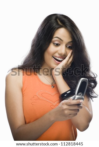 Shocked young woman reading text message - stock photo