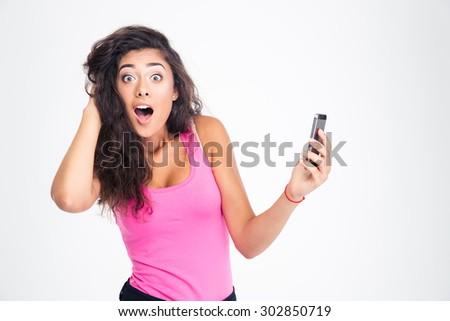 Shocked young woman standing with smartphone and looking at camera isolated on a white background - stock photo