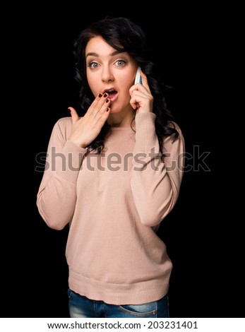 Shocked young woman talking on cell phone on black background - stock photo