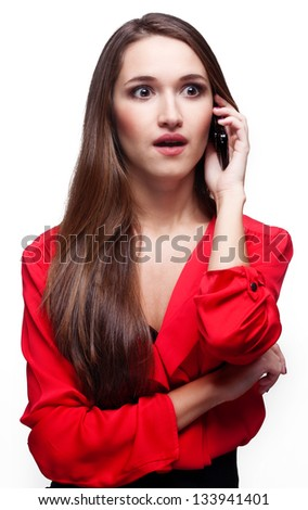 Shocked young woman talking on the phone on white background - stock photo