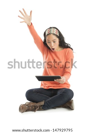 Shocked young woman with hand raised looking at digital tablet while sitting against white background