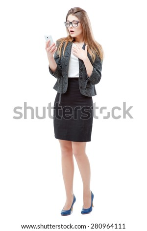 Shocking news! Business and technology. Full length of surprised young woman in formal wear using smart phone. Isolated on white. - stock photo