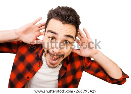 Shocking news. Portrait of surprised young man in shirt smiling while standing against white background - stock photo
