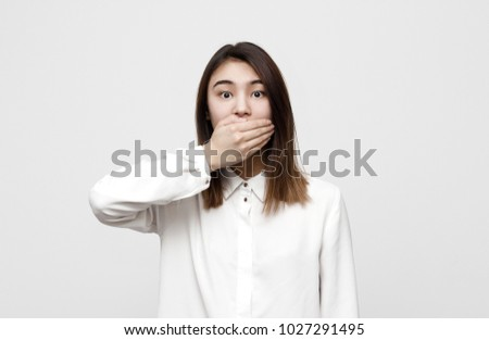 Shocking news. Surprised young attractive woman covering mouth with hand in formal white shirt staring at camera.