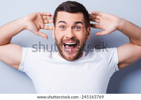 Shocking news. Surprised young man expressing positivity and gesturing while standing against grey background - stock photo