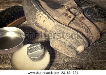 Shoe care. Shoe wax, boot and brushes on wooden surface. Edited image with vintage effect - stock photo