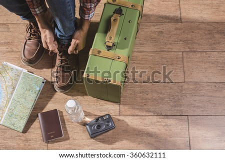 Shoe laces and luggage on wooden floor for travel concept. - stock photo