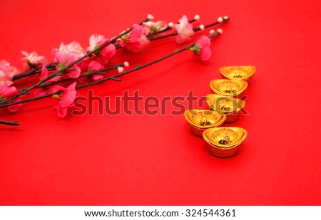 "Shoe-shaped gold ingot (Yuan Bao) (with the words ""zhao cai jin bao"" meaning money come in) and Plum Flowers on red background with copy space - best for Chinese New Year use"