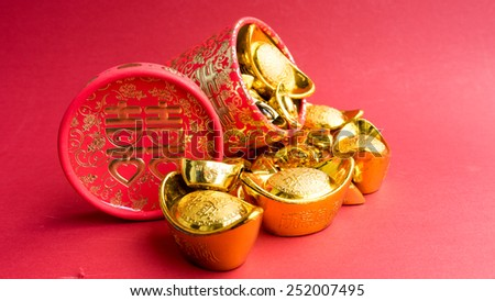 Shoe-shaped metal gold ingot (Yuan Bao) and Chinese wedding gift box. Concept for Chinese Lunar New Year auspicious symbol. Slightly defocused and close-up shot. Shot with natural light. Copy space. - stock photo