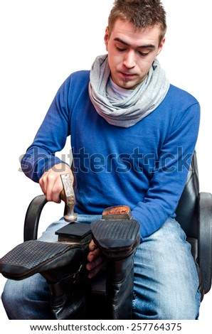 Shoemaker repairing a shoe on white background - stock photo