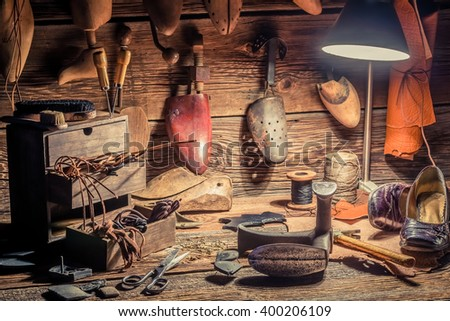 Shoemaker workshop with brush and shoes - stock photo