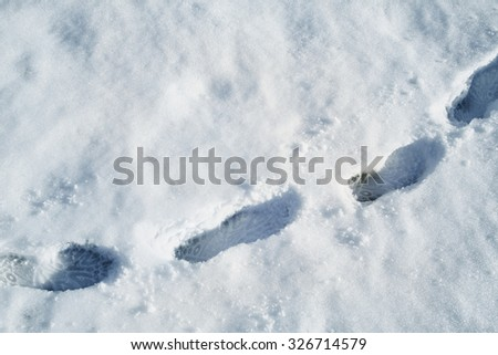 Shoeprints in sunny fresh snow on snowy meadow with copy space background. - stock photo