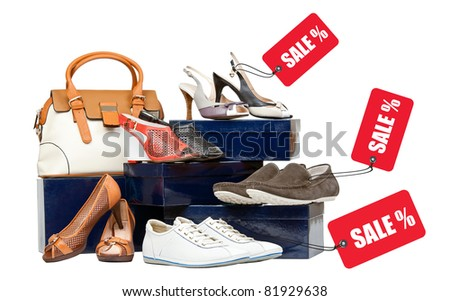 Shoes and handbag on boxes, sale tags attached to shoes - stock photo