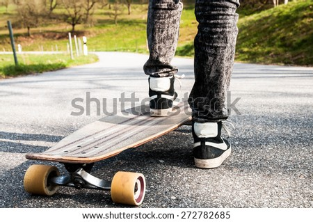 Shoes and legs of a young boy in black jeans on a longboard on a rural street - stock photo