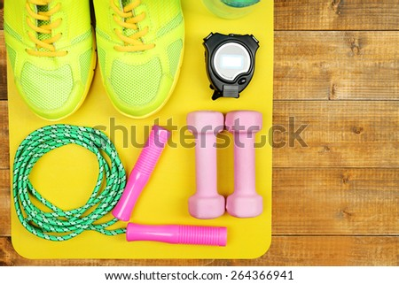 Shoes and sports equipment on mat on wooden floor, top view - stock photo