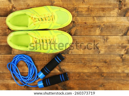 Shoes and sports equipment on wooden floor, top view - stock photo
